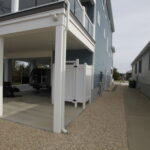 Teal Bliss Waterfront newly constructed home in Swann Keys side exterior concrete carport